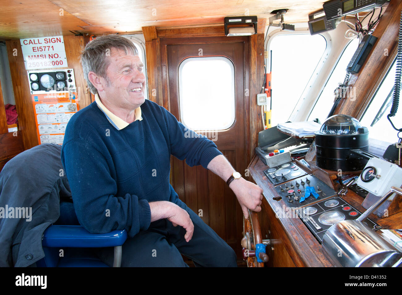 Ferryman steering ferry from Baltimore to Cape Clear Island, County Cork, Ireland - Stock Image