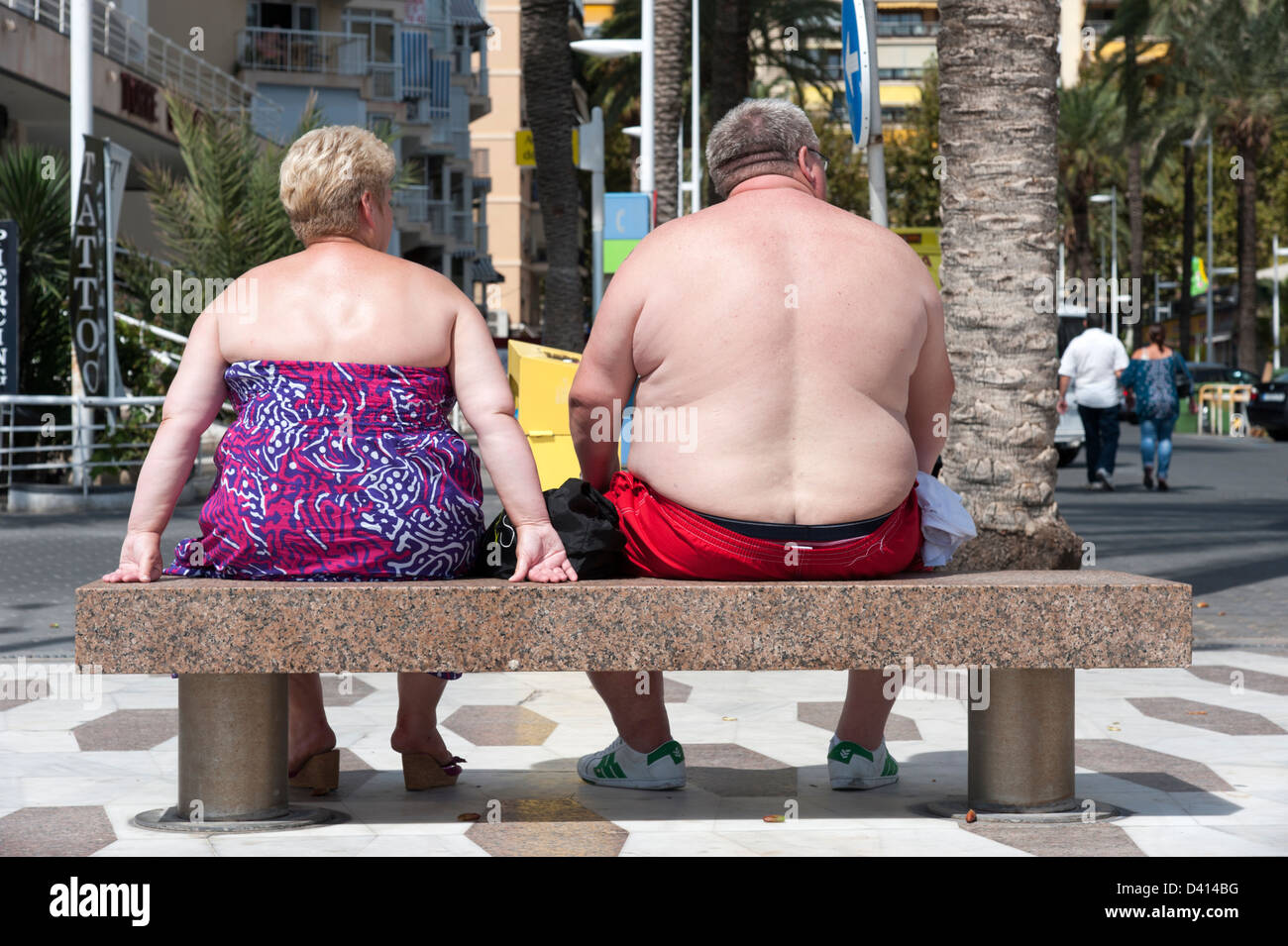 Overweight British couple on the waterfront in Benidorm, Costa Blanca, Spain - Stock Image