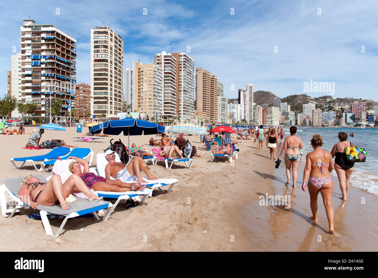 Tourists relaxing on deckchairs at the beach, Benidorm, Costa Blanca, Spain - Stock Image