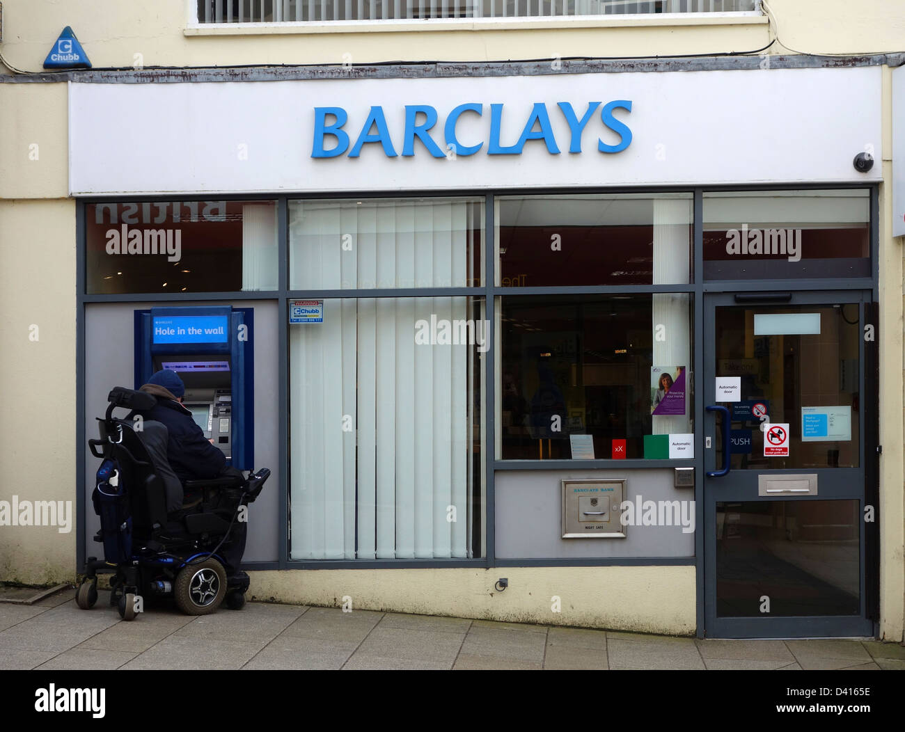 A  disabled customer using the atm at a Barclays Bank - Stock Image