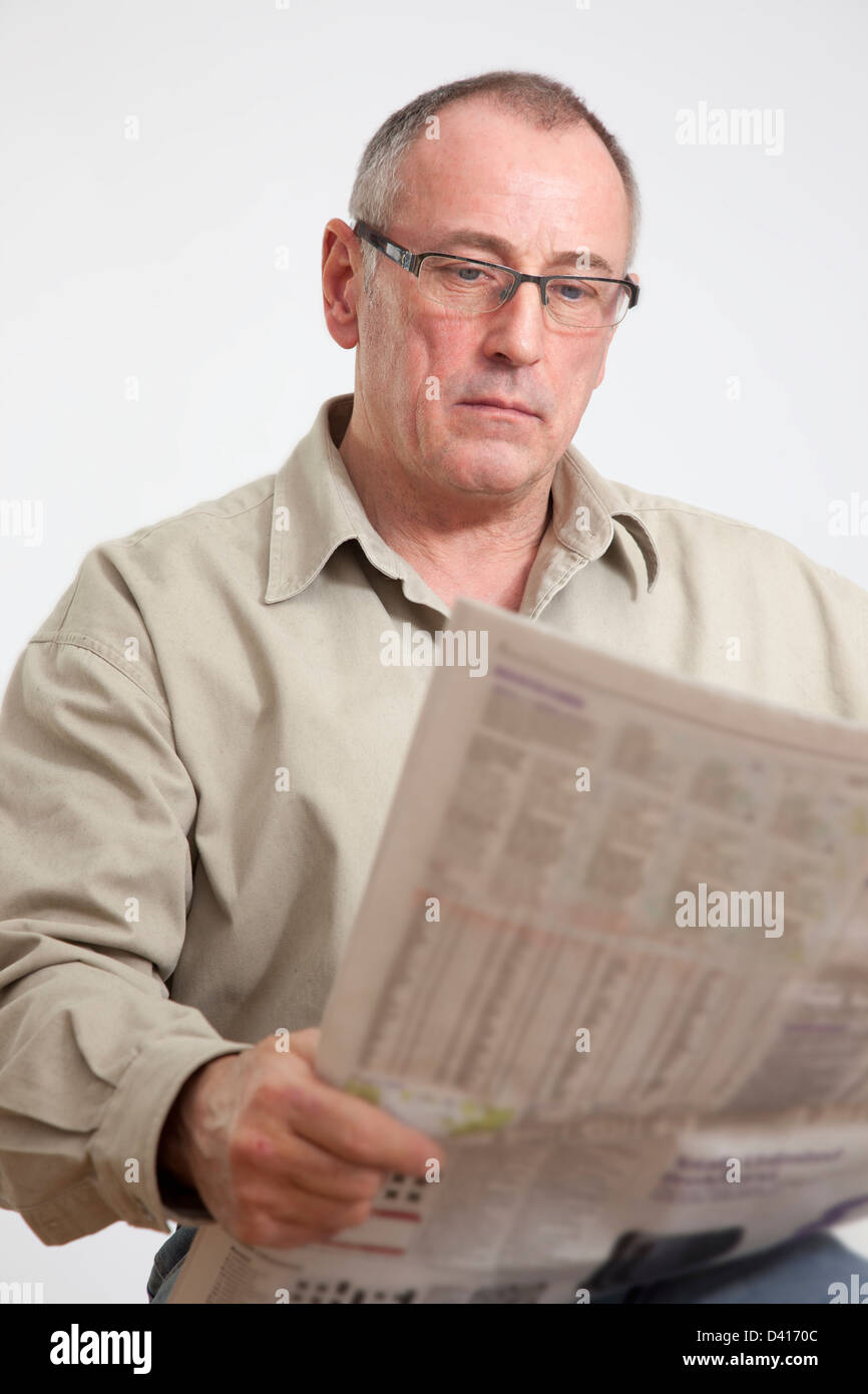 Mature man in 50s, reading a broadsheet newspaper. - Stock Image