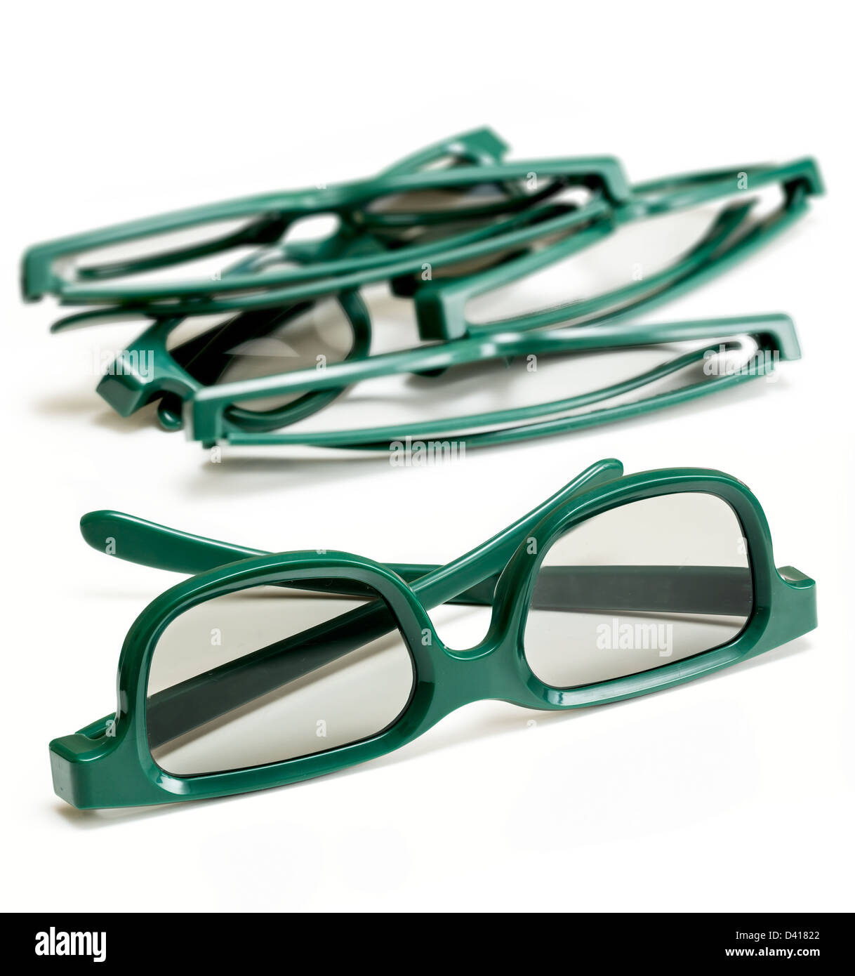 Pair of green 3d polarized glasses for watching 3-d movies in cinema isolated against white with stack of used specs - Stock Image