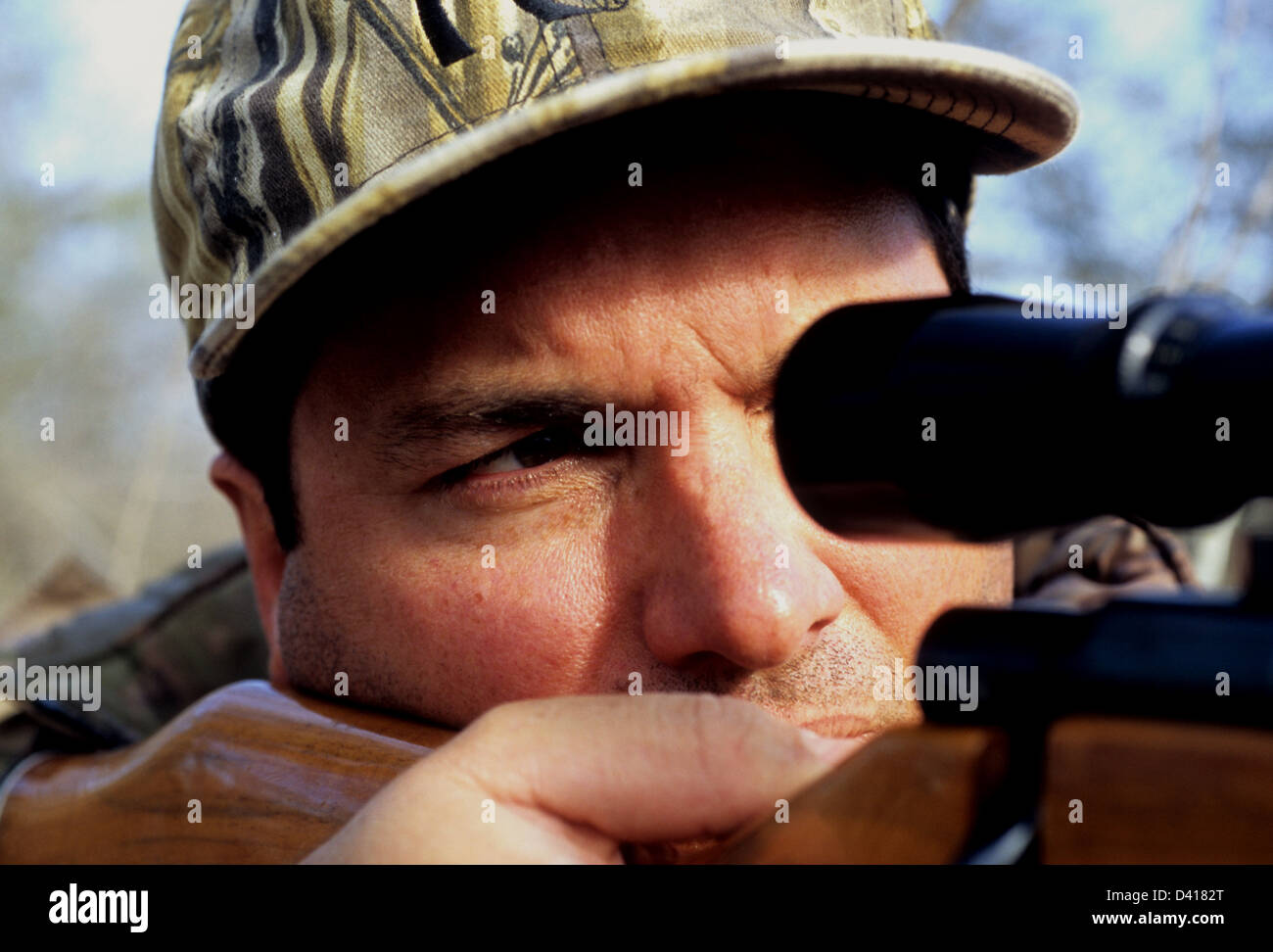 A South Texas deer hunter looking through his scope and aiming a rifle - Stock Image
