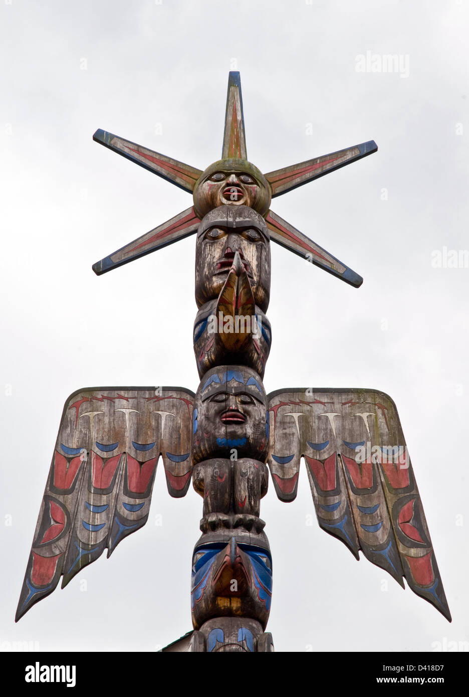 A totem pole carved in the Nuxalk tradition in the Great Bear Rainforest, in the town of Bella Coola, British Columbia, - Stock Image