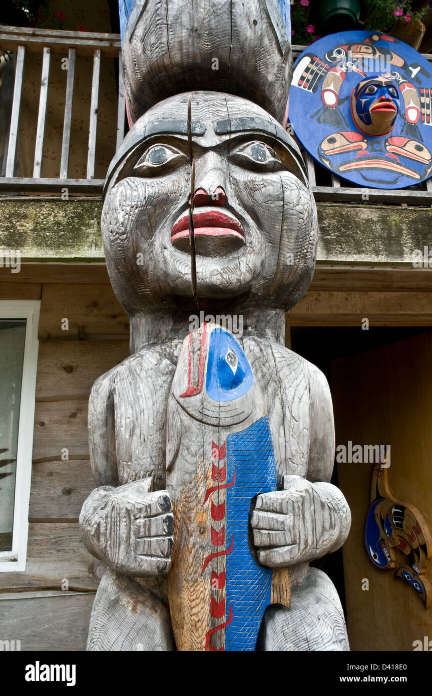 Part of a totem pole carved in the Nuxalk tradition in the Great Bear Rainforest, in the town of Bella Coola, British - Stock Image
