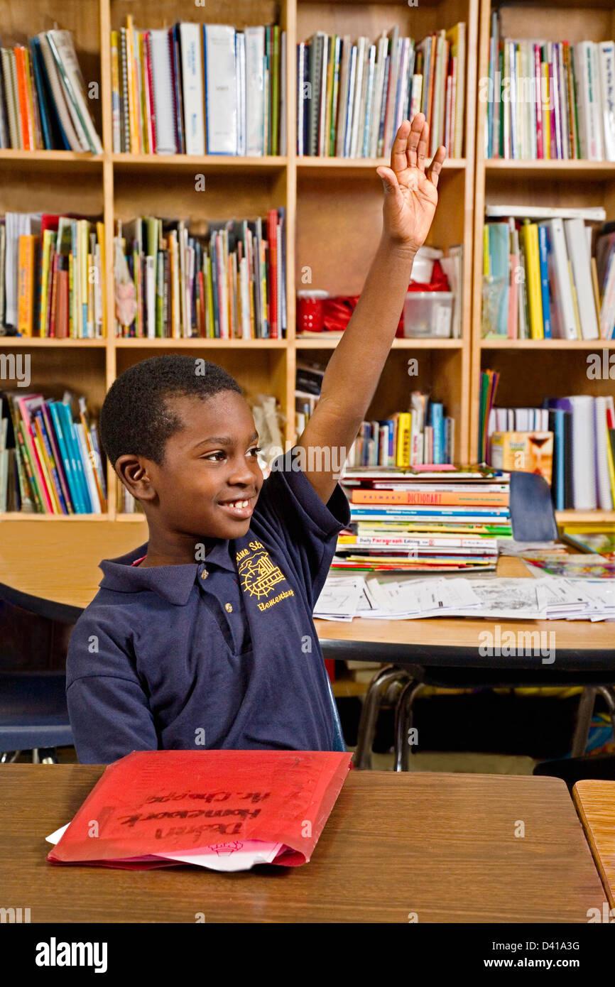 Black second grade male student sits at desk and raises his hand in Louisiana school - Stock Image