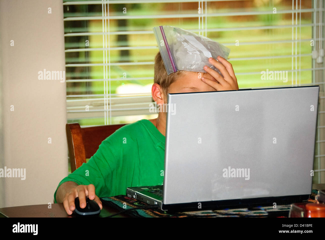 Young boy on laptop with icebag on head for his stressful headache. - Stock Image