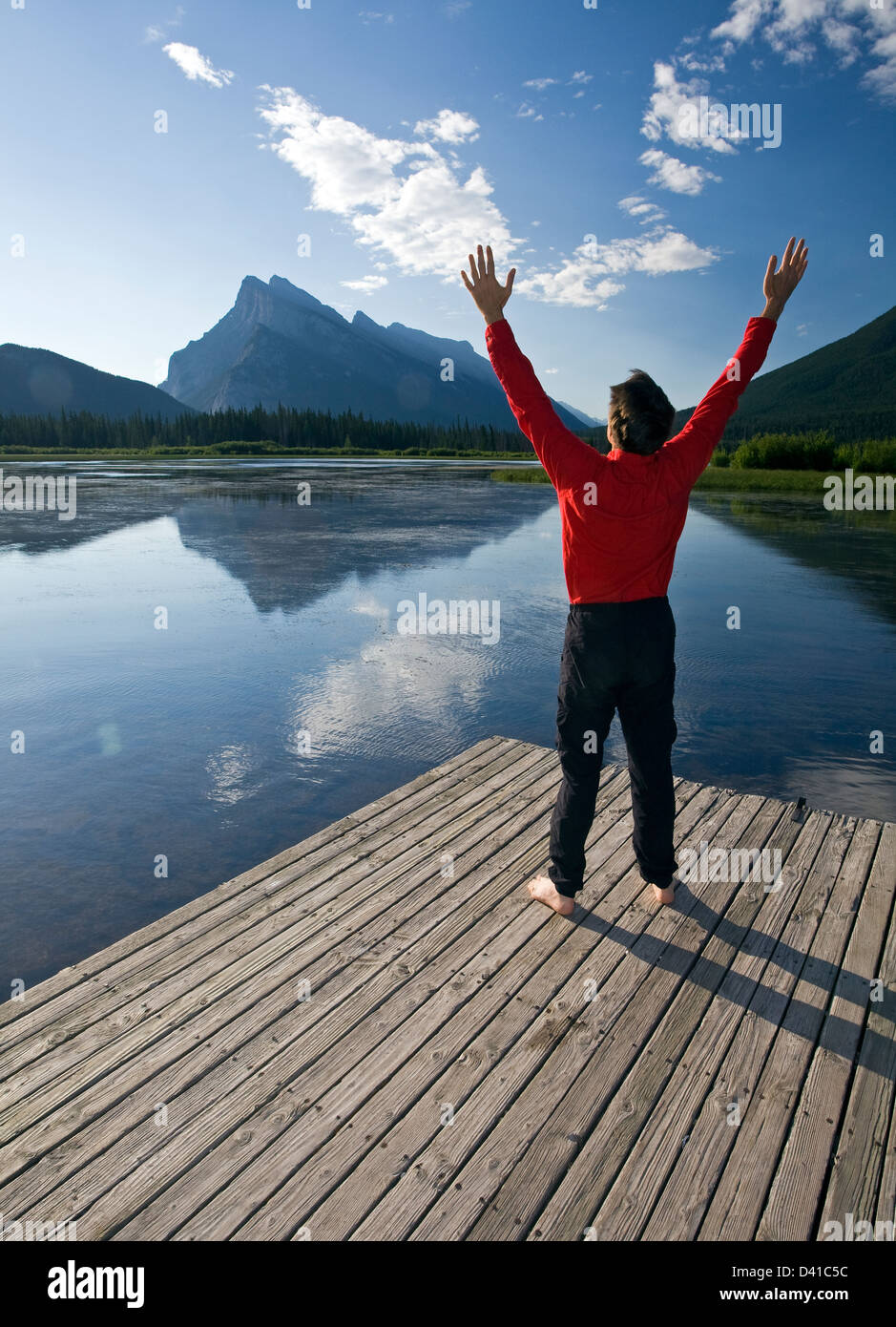 54 year old male saluting the sun on a dock at Vermillion Lake, Banff, Alberta, Canada. - Stock Image