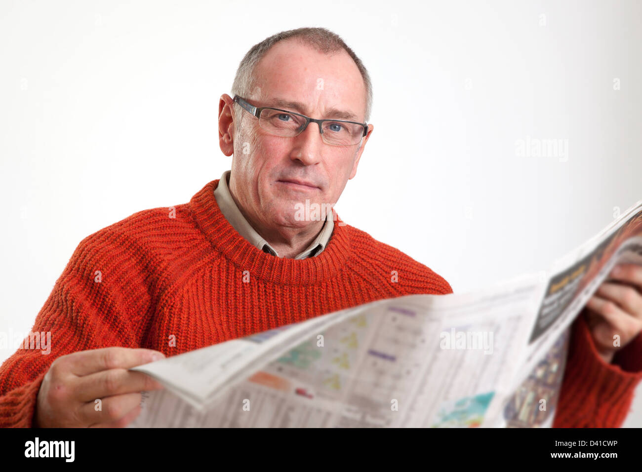 Mature man in 50s wearing sweater, reading a broadsheet newspaper, looking to camera serious. - Stock Image