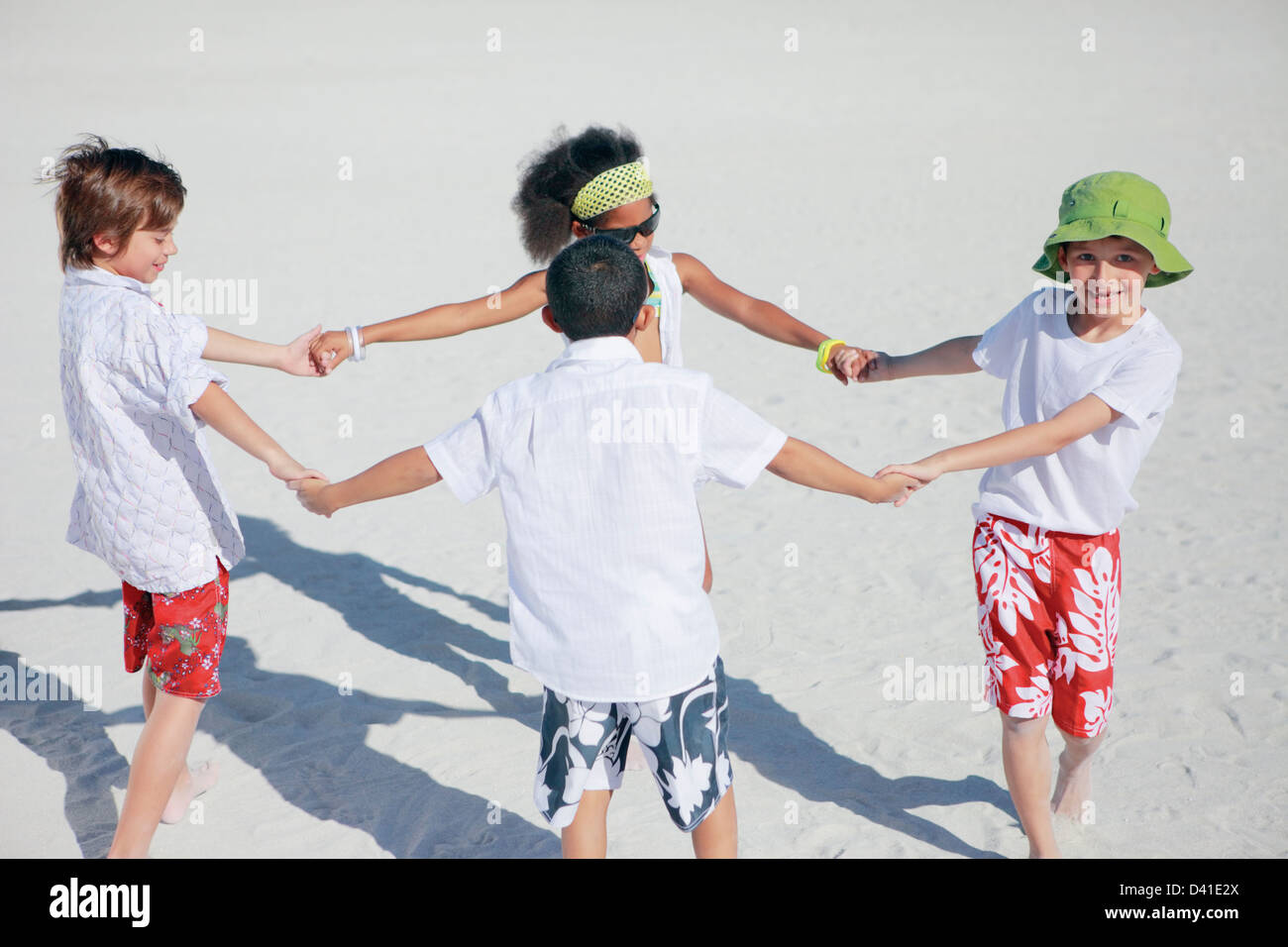 a group of kids holding hands and running around in circles, on a bright summer day at the beach - Stock Image