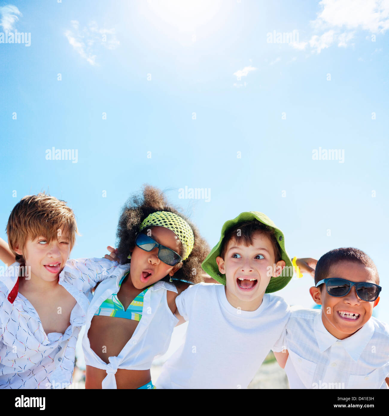 school-age children having fun on a sunny day at the beach, making faces - Stock Image
