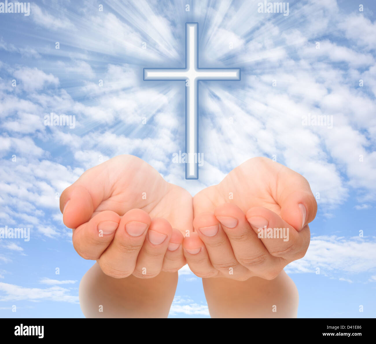 Hands holding Christian cross with light beams over sky Stock Photo