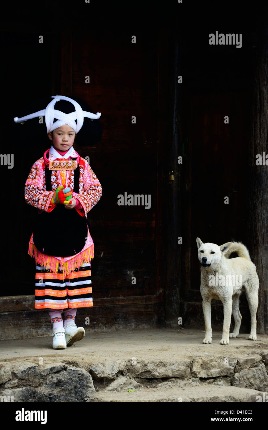 A Long Horn Miao little girl in traditional costume standing with her pet dog by her home. - Stock Image