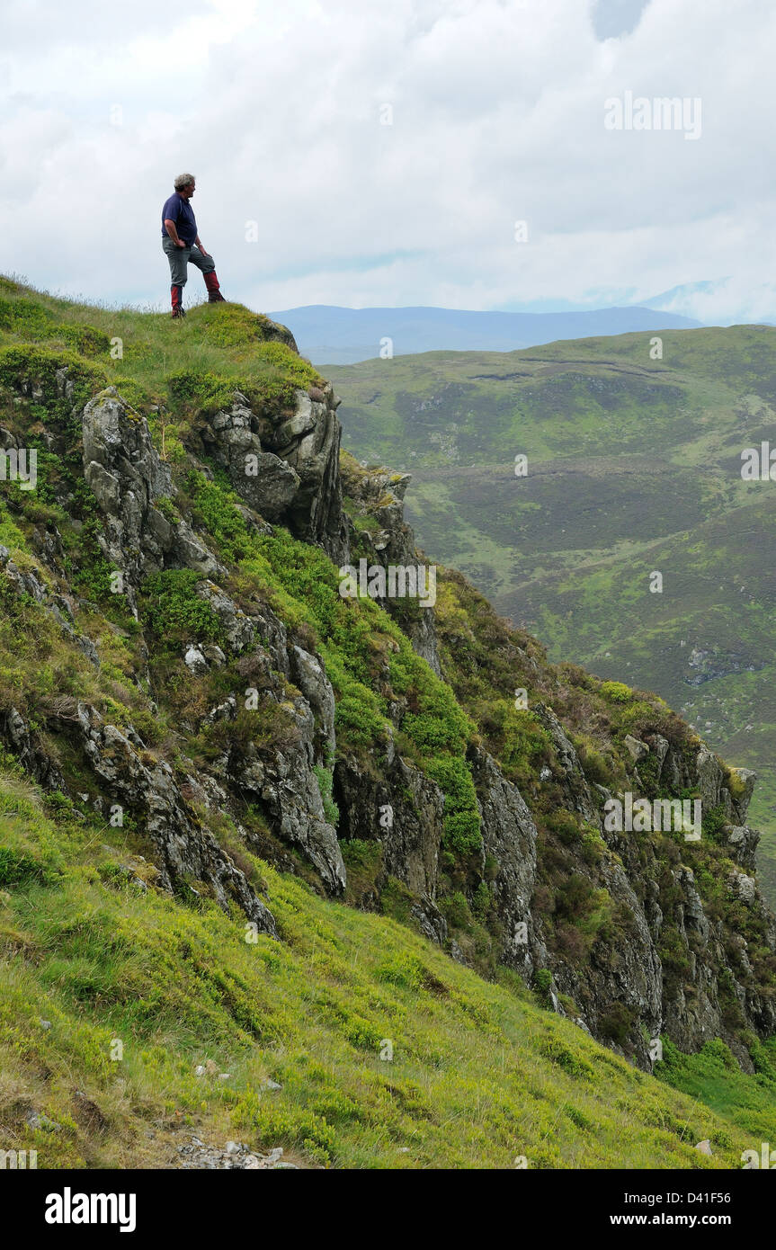 A hillwalker stands on the ridge of the Corbett Beinn Each in Stirlingshire - Stock Image