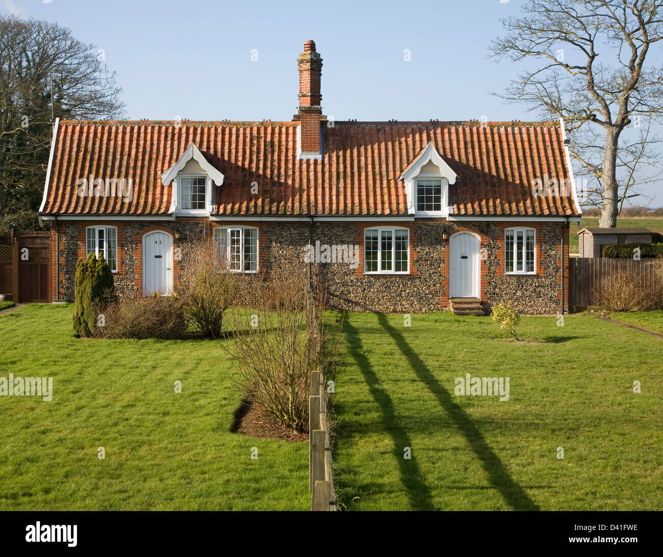 Small symmetrical estate cottages and gardens divided by fence, Suffolk, England - Stock Image
