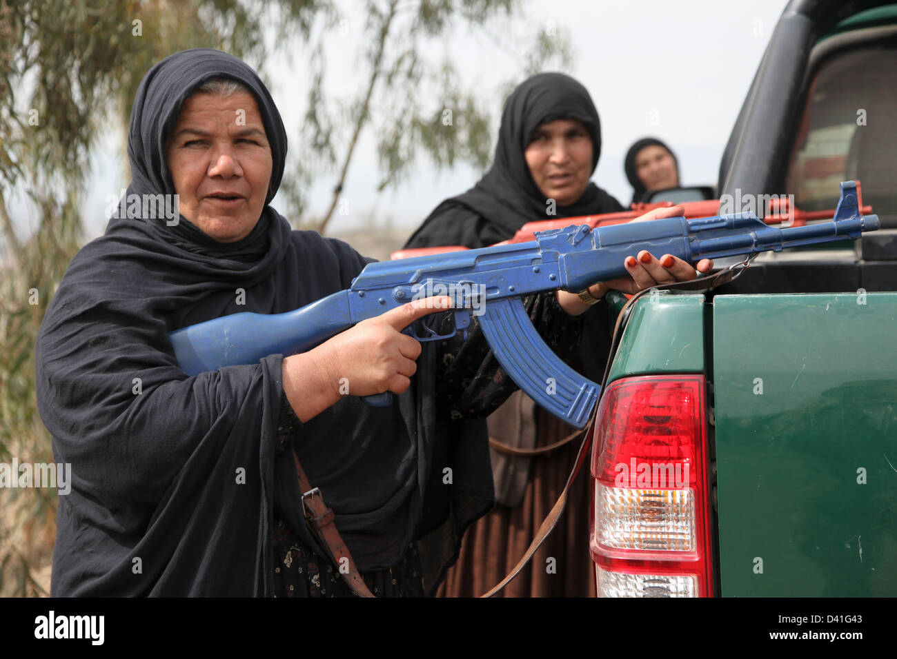 Women Afghan Uniform Police wield training weapons and take cover behind a police vehicle while conducting a high - Stock Image