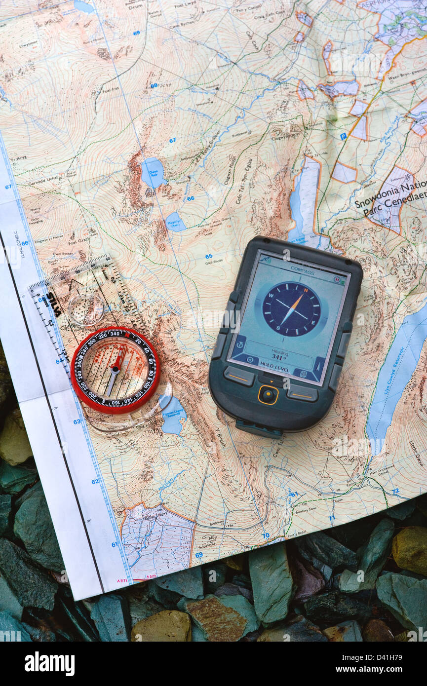 A magnetic compass and a GPS unit on a map. - Stock Image