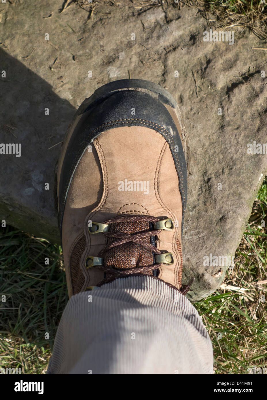 Close up of walking boot on the step of a stone stile on a public footpath, UK - Stock Image
