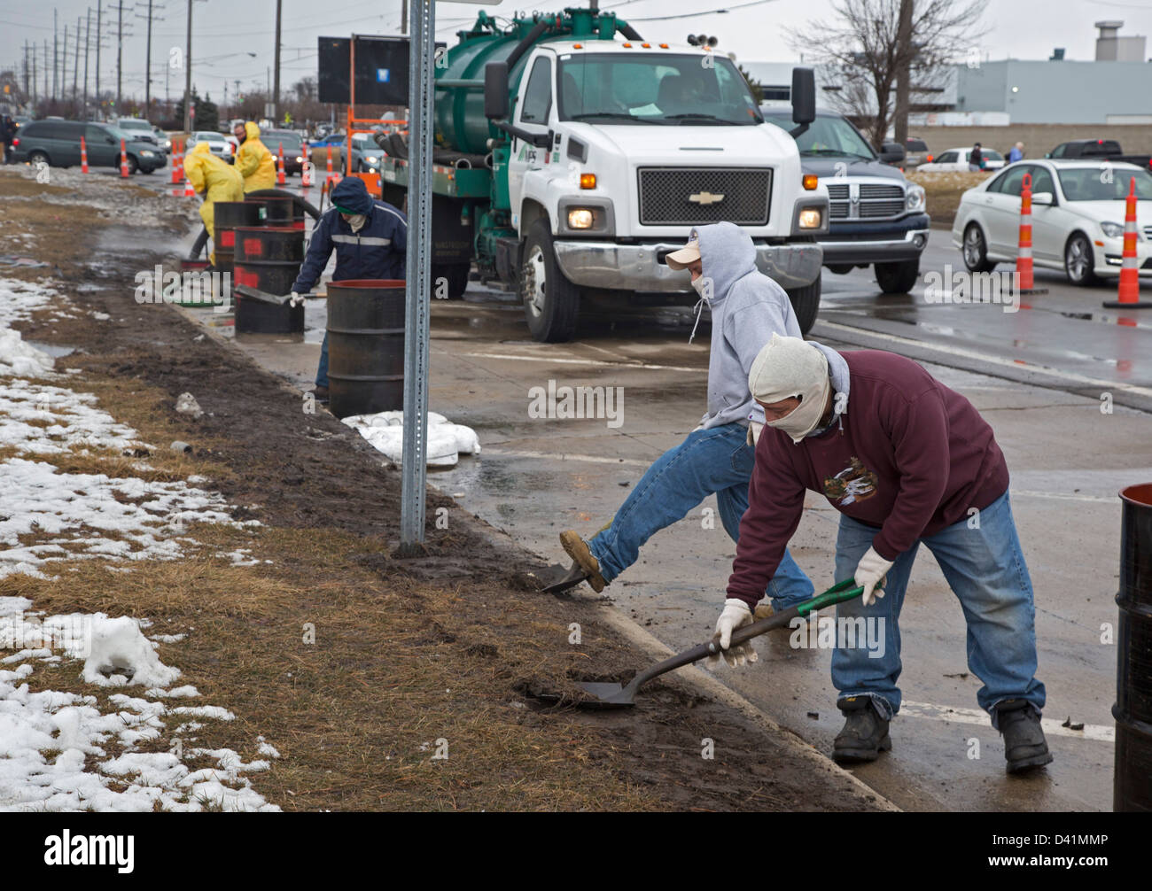 Warren, Michigan - Workers clean up a hazardous material spill on the shoulder of a major street. - Stock Image