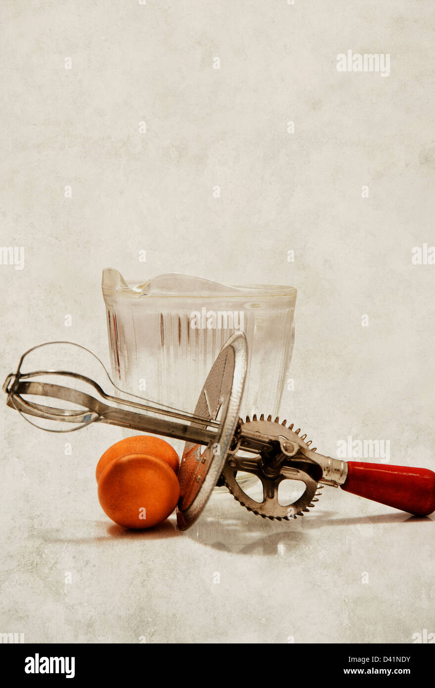 Old fashioned hand food mixer or beater beside eggs - Stock Image