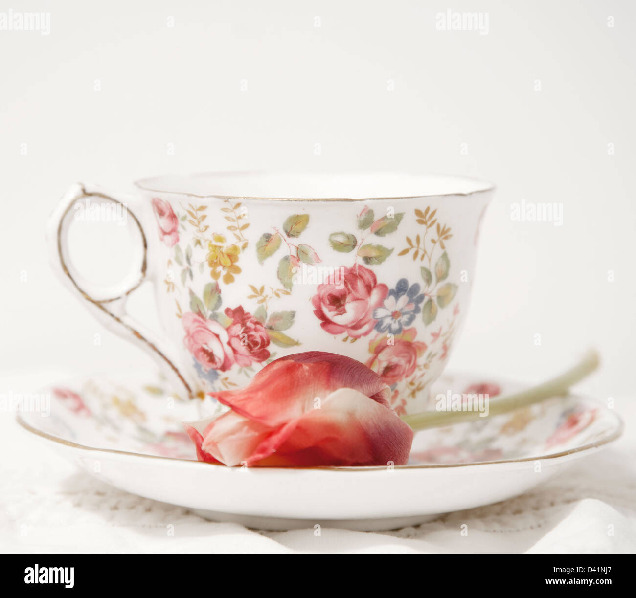 Flowered porcelain tea cup and saucer with tulip on saucer - Stock Image