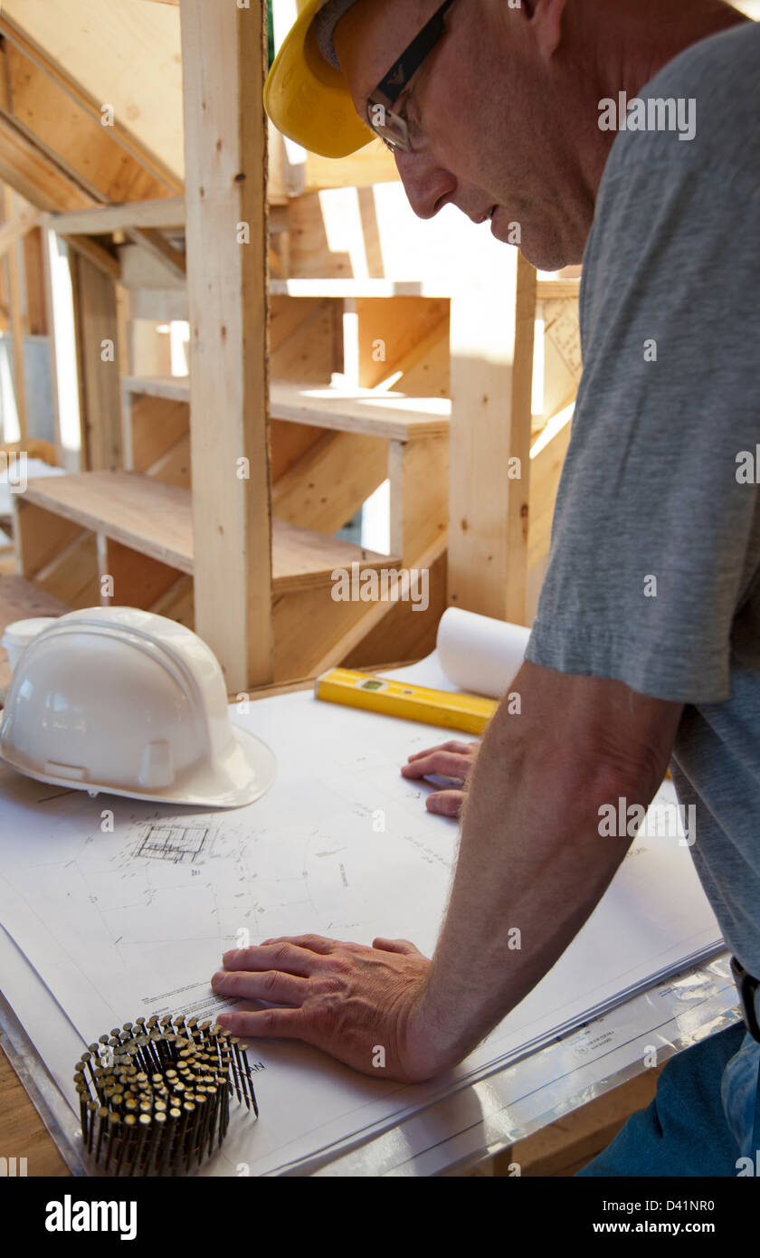 Man with hard hat in construction zone looking at blueprints - Stock Image