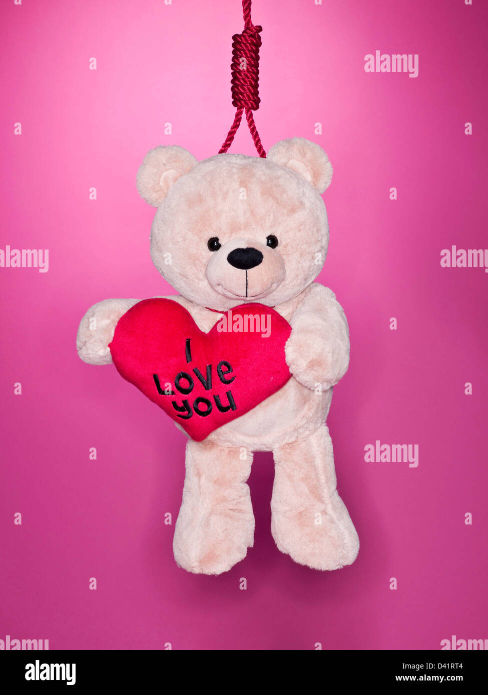 Teddy bear holding love heart with noose round neck - Stock Image