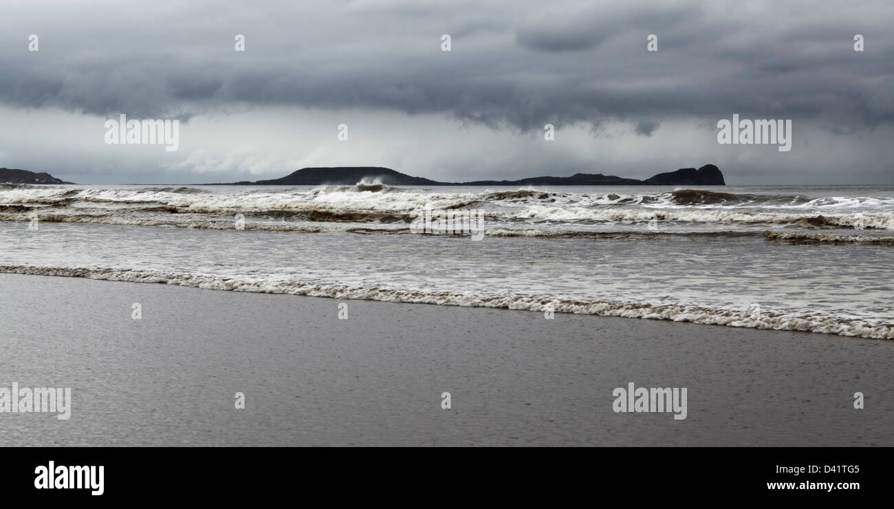 A dark stormy Sky looming above Worms Head on the Gower peninsula - Stock Image