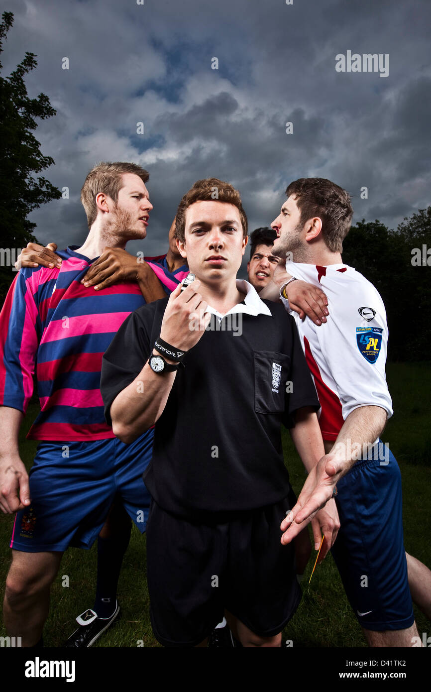 Referee with red card with angry football players - Stock Image