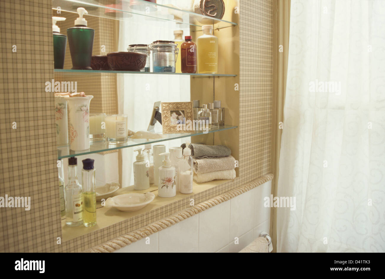 Glass Perfume Bottles And Toiletries On Glass Shelves In Modern Bathroom