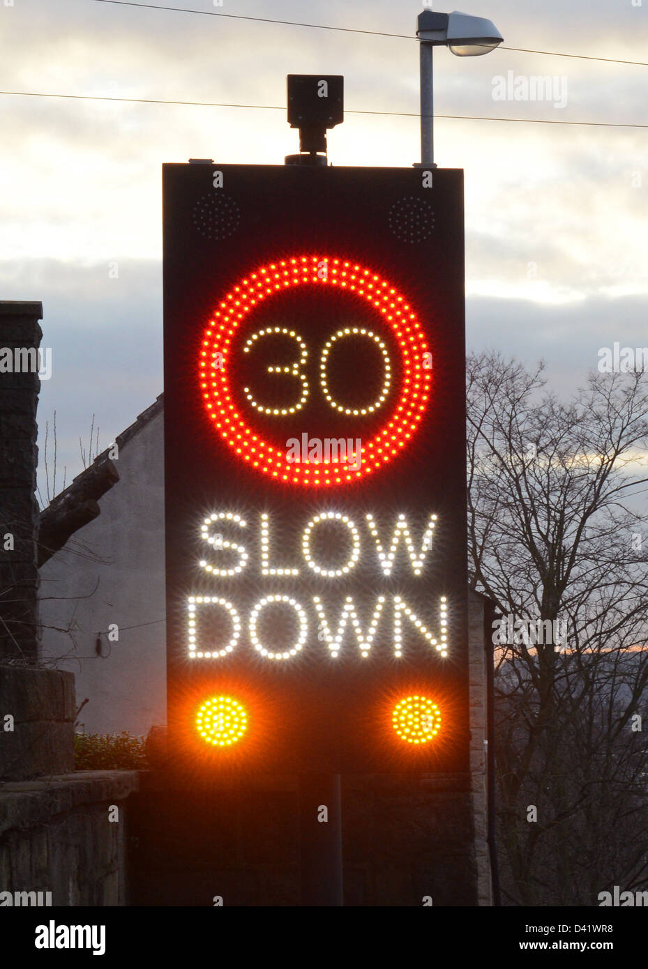 slow down warning roadsign triggered by approaching vehicles at dusk, south elmsall, yorkshire, united kingdom - Stock Image