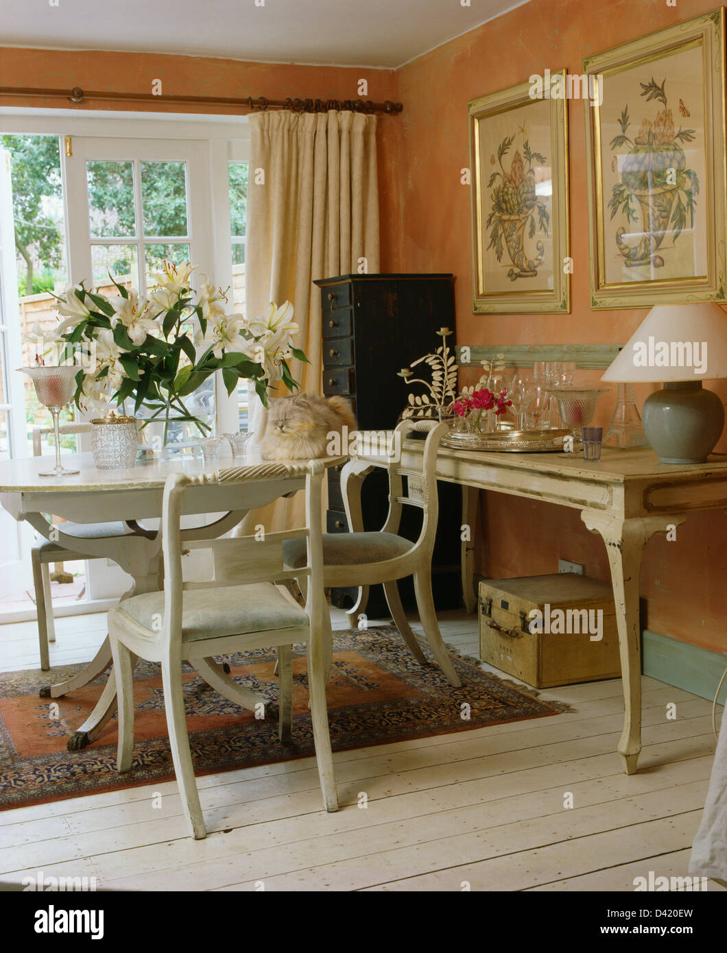White painted table and chairs in peach cottage dining room with ...