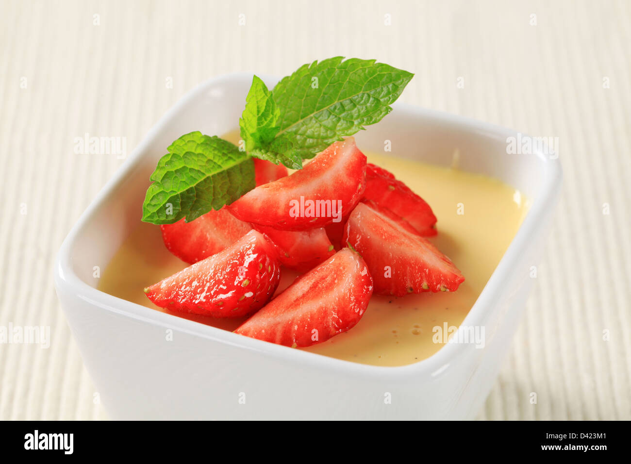 Small dish of vanilla pudding topped with strawberries - Stock Image