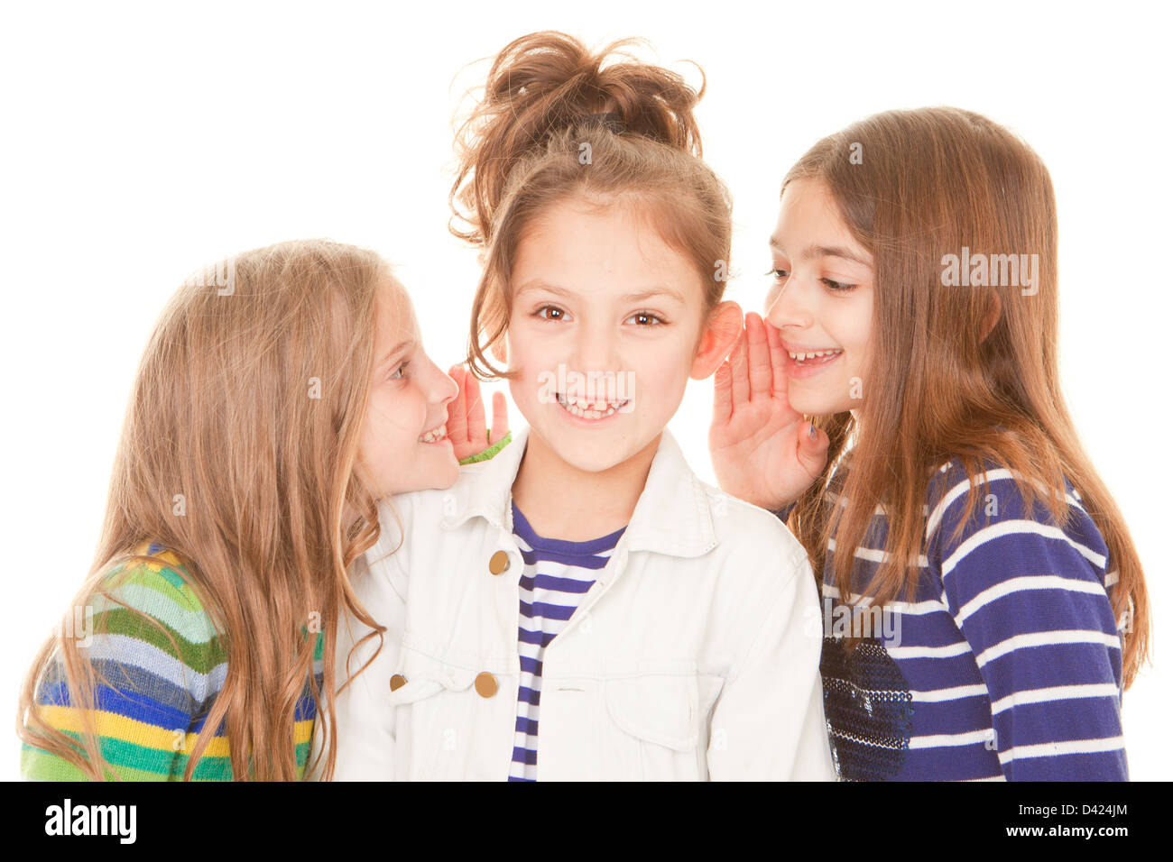 friends whispering secrets to happy child Stock Photo