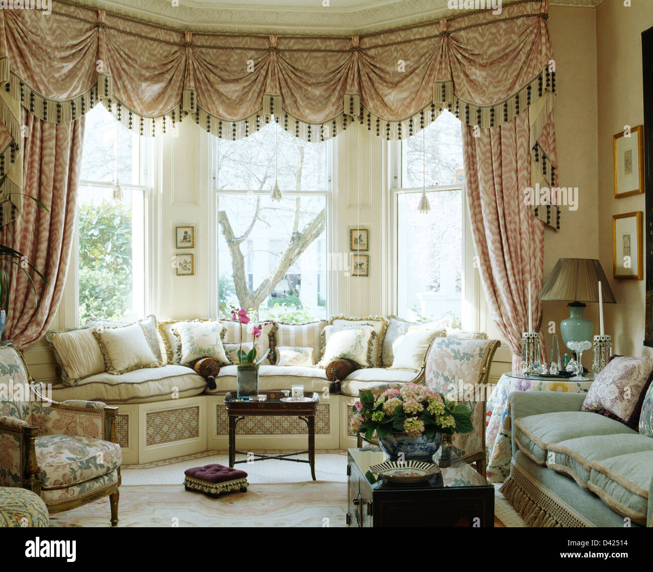 Swagged+tailed Silk Curtains On Bay Window Above Window Seat With Cream  Cushions In Townhouse Drawing Room With Comfortable Sofa