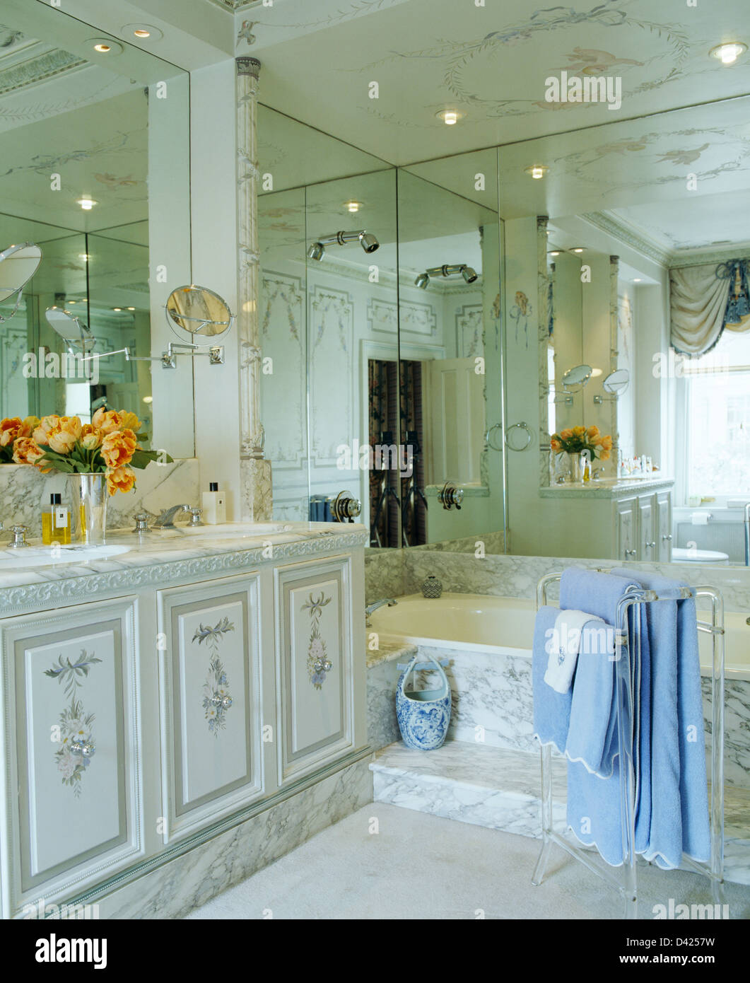 Mirrored walls and marble paneled bath in townhouse bathroom with ...