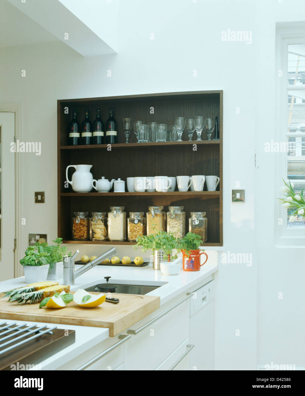 Cups and glasses with glass storage jars on black recessed shelves above sink in modern white kitchen - Stock Image