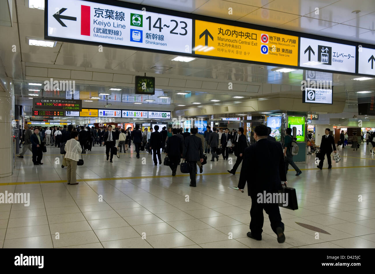 People coming, going and passing through one of many underground levels inside Tokyo train station. - Stock Image