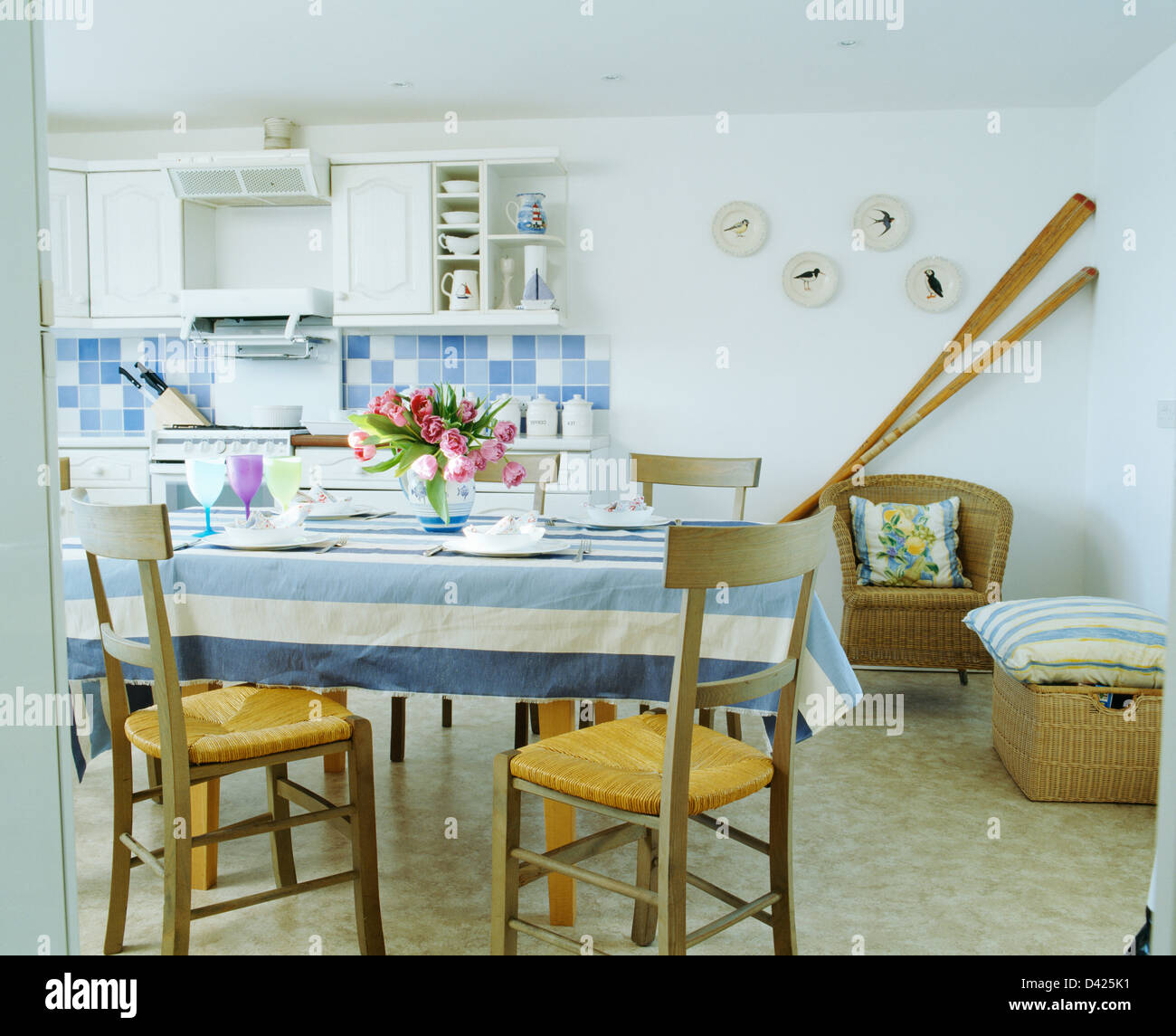 Rush-seated chairs at table with blue+white striped cloth in white ...