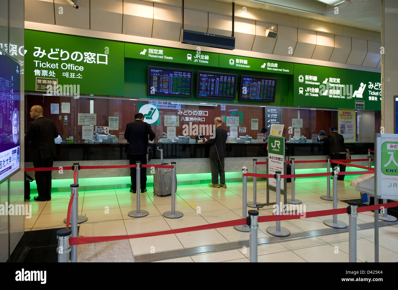 Businessmen buying tickets at one of several ordinary train and shinkansen bullet train ticket sales windows at - Stock Image
