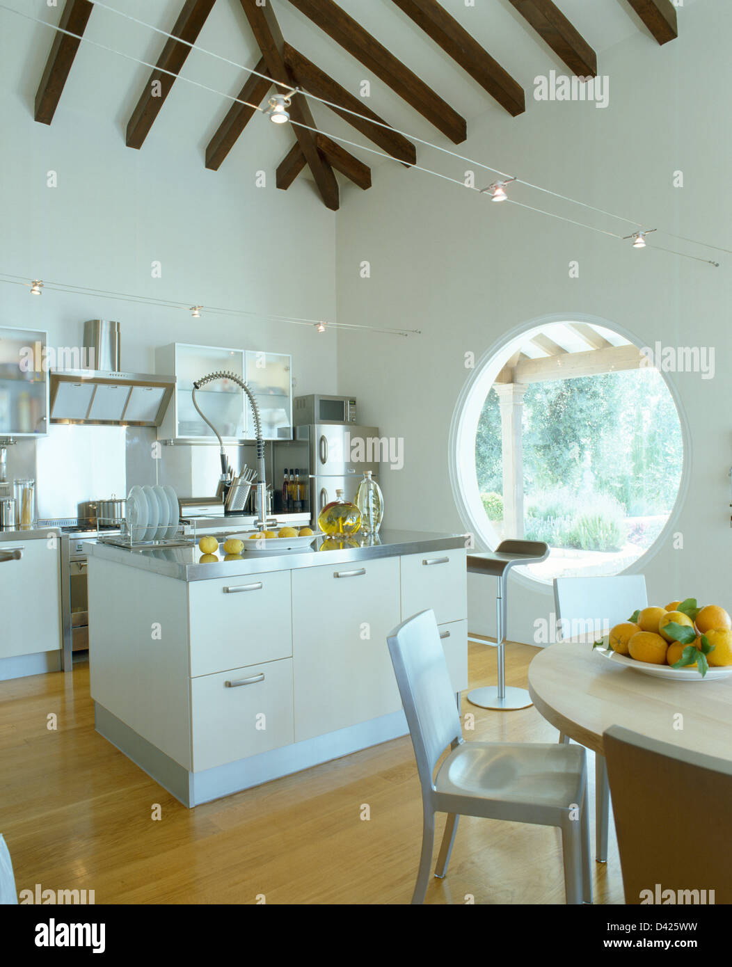 Island Unit In Modern White Mediterranean Kitchen Dining Room With Large Circular Window And Wooden Flooring