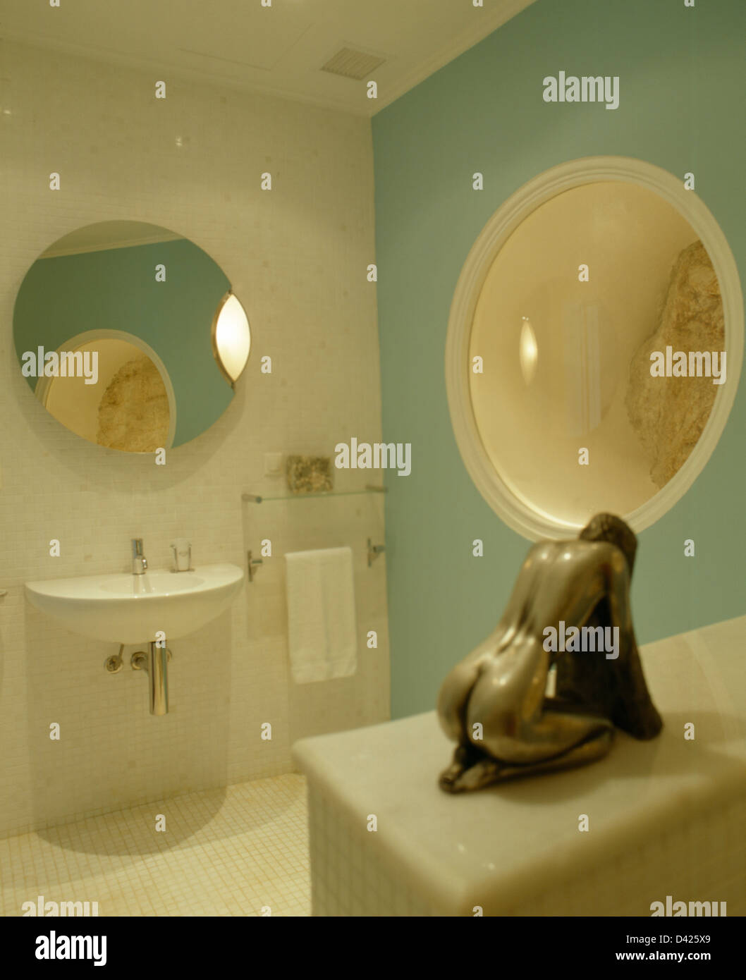 Bronze Statue In Modern Pastel Turquoise Bathroom With Circular Mirror Above Basin And Large Alcove