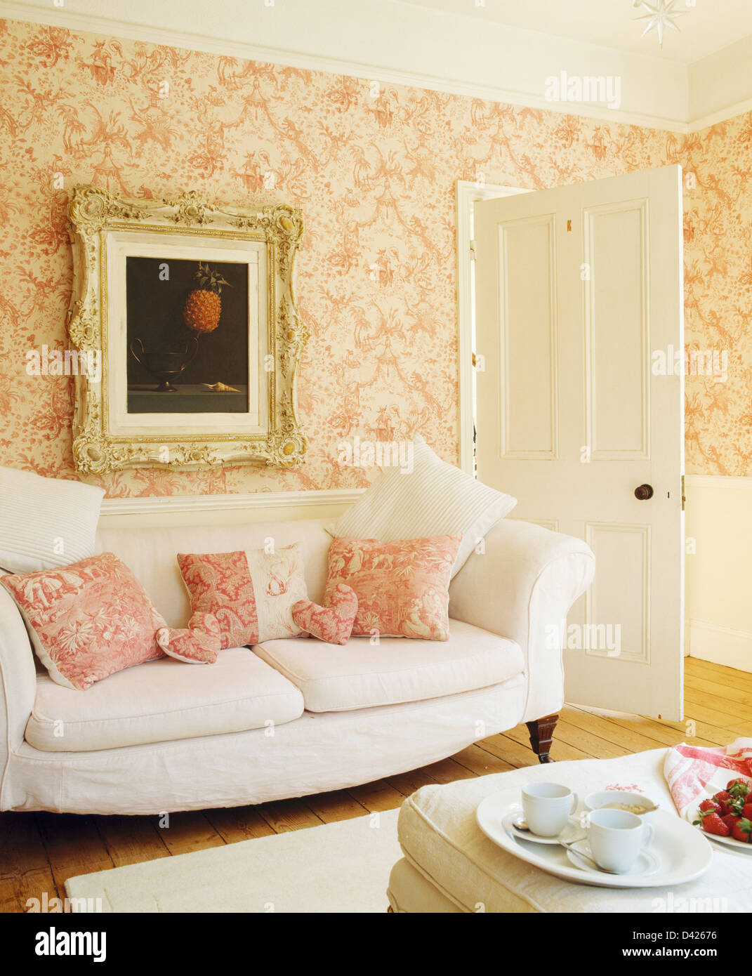 Ornately framed picture above white sofa with pink patterned ...