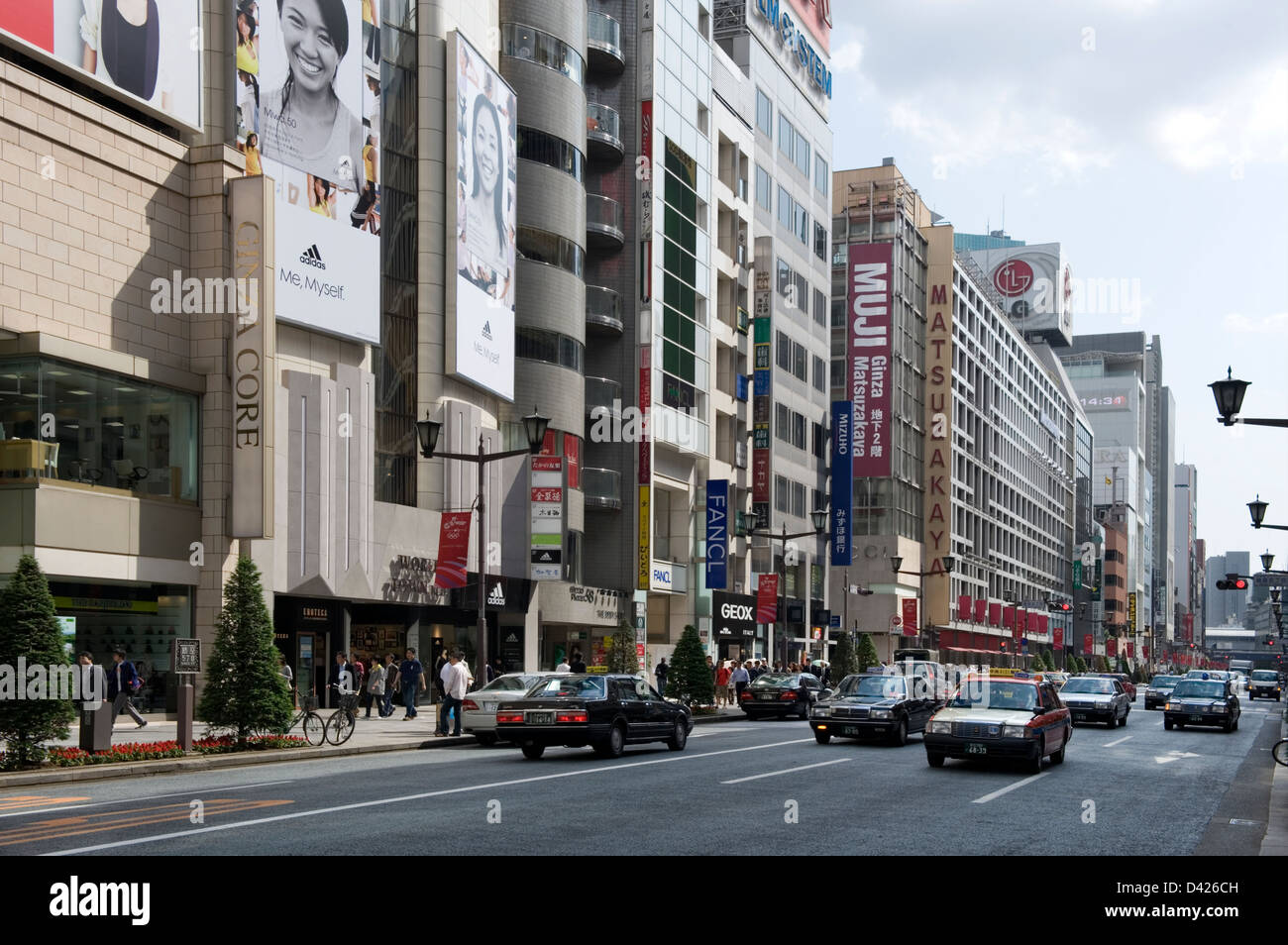 Retail stores and fashion boutiques line both sides of Chuo-dori (Central Street) in upscale Ginza shopping district - Stock Image