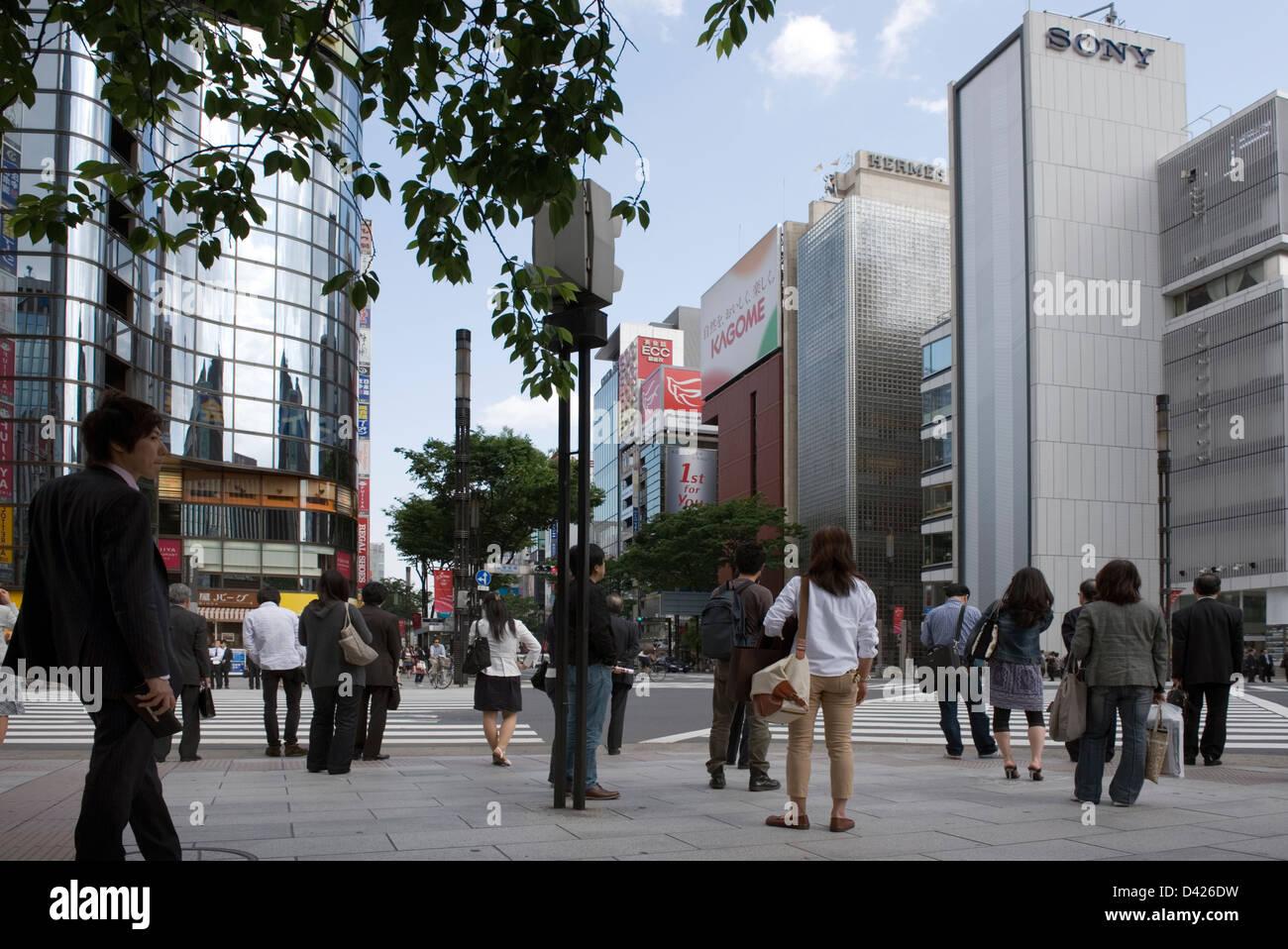 Pedestrians on the corner of Harumi-dori and Sotobori-dori streets in the upscale shopping district of Ginza, Tokyo. - Stock Image