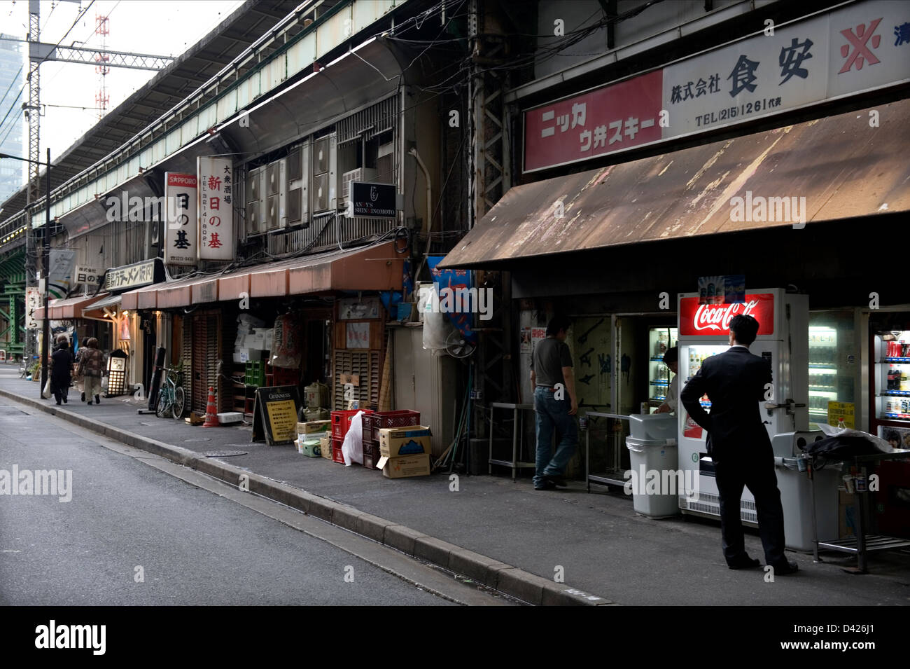 Shops and restaurants share space side-by-side under the elevated railway tracks in Tokyo's Yurakucho district. - Stock Image