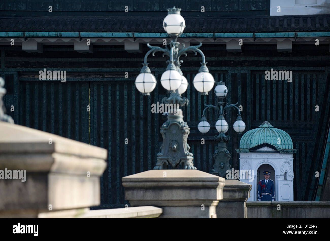 An Imperial Palace guard stands watch at the Nijubashi Bridge gate, once part of Edo Castle in the heart of Tokyo. - Stock Image