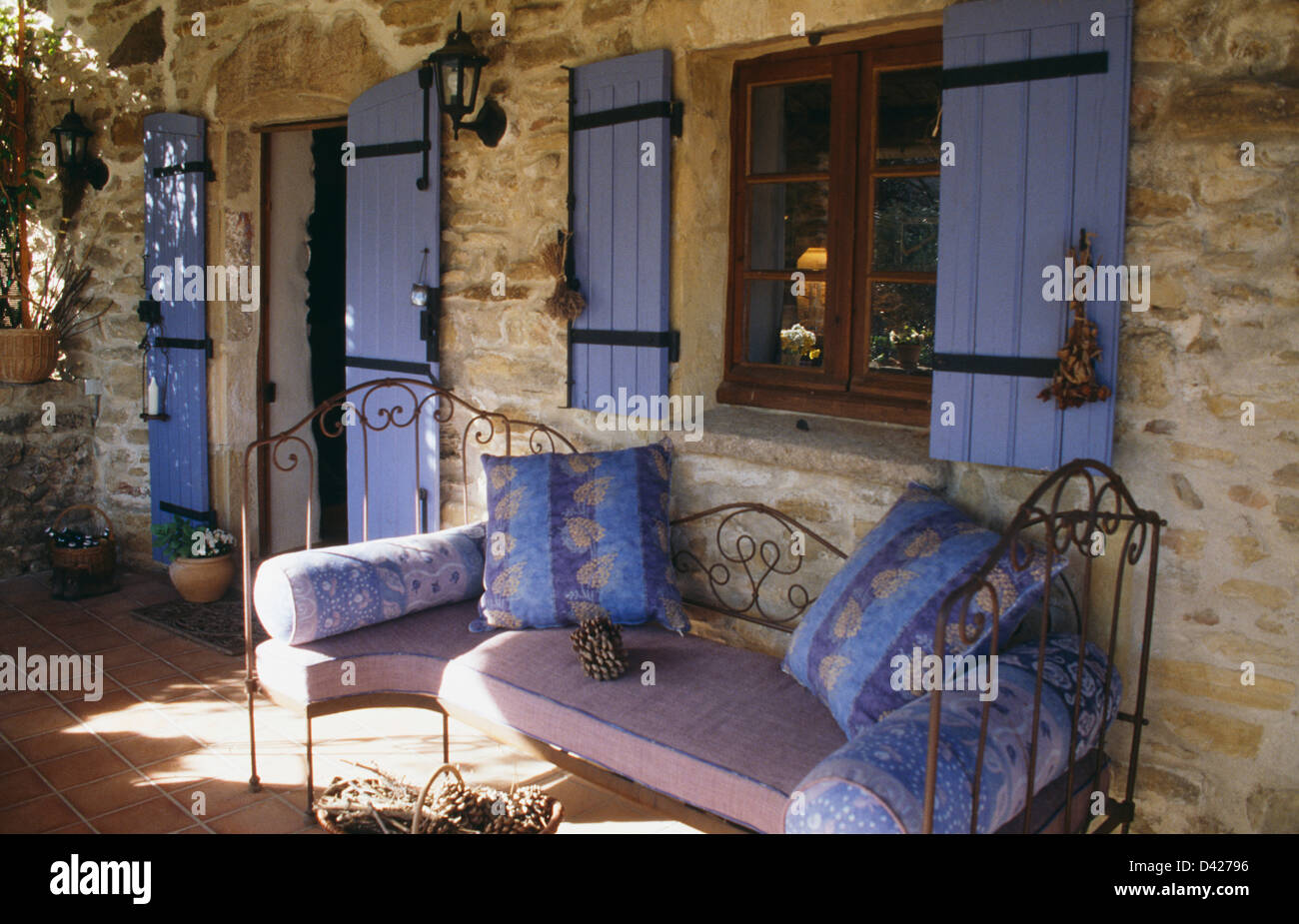 Blue Cushions On Wrought Iron Daybed Below Window With Blue Shutters