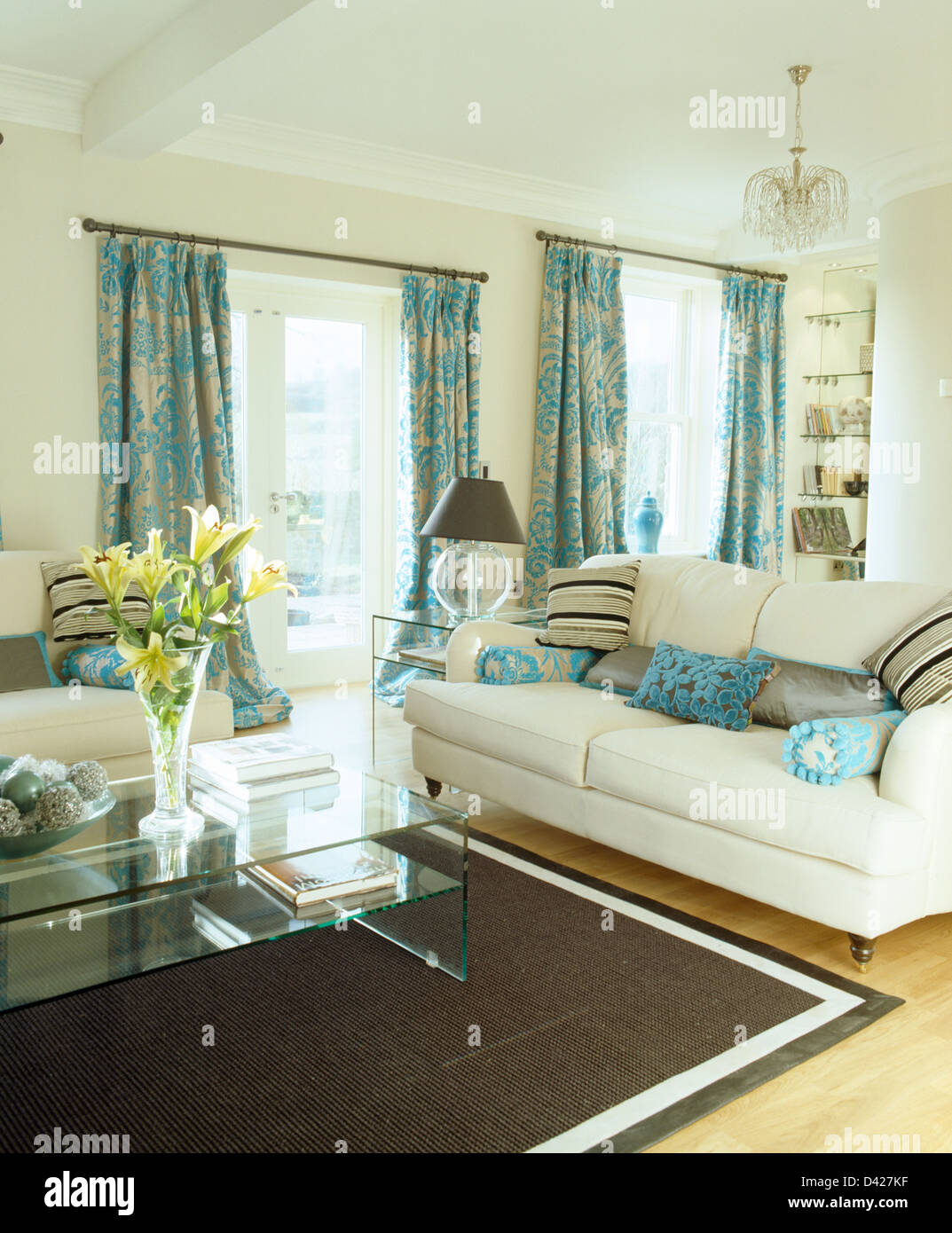 Patterned turquoise curtains and cream sofas in cream living room ...