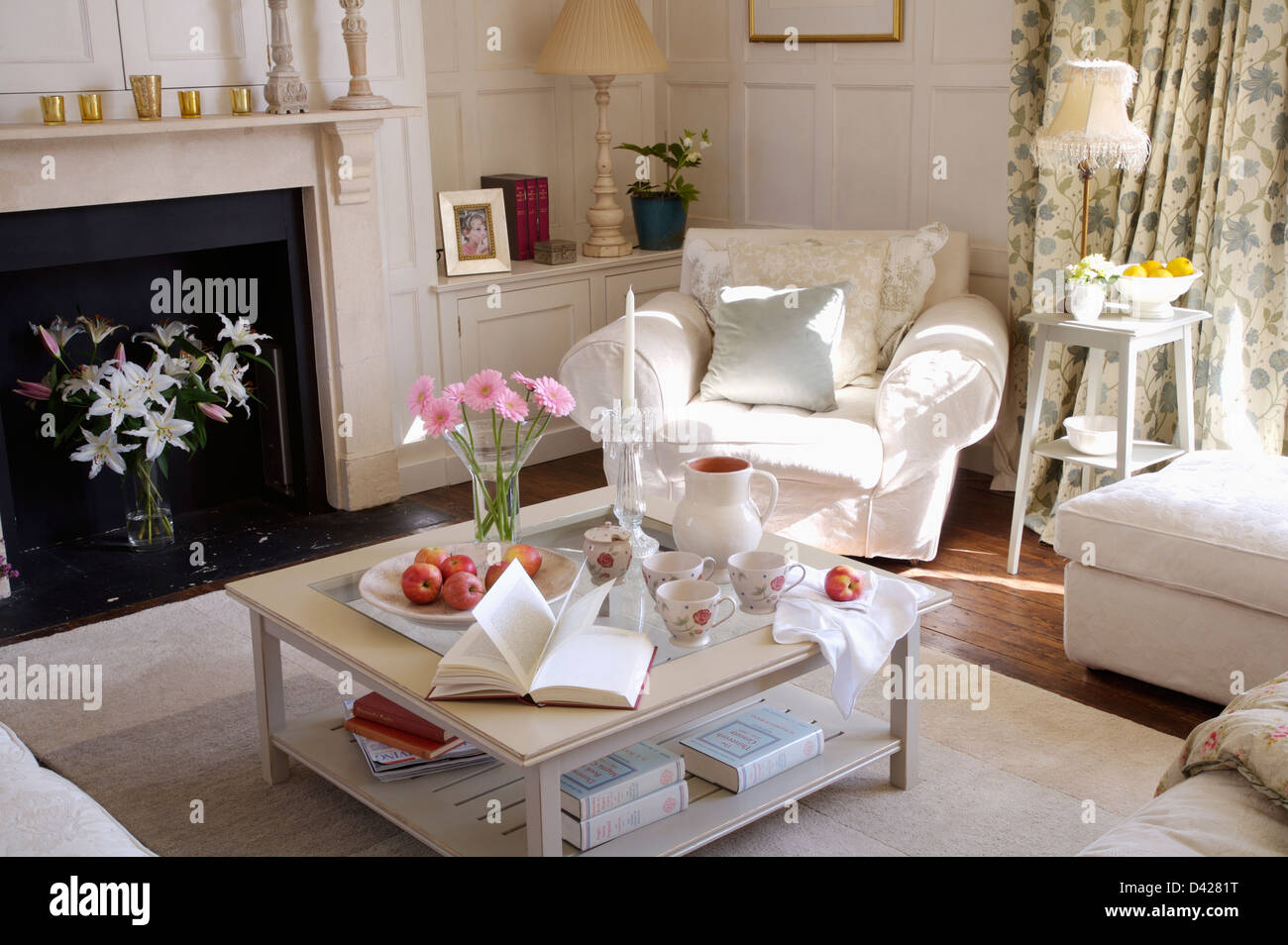 Book and cups on two-tier table in white living room with ...